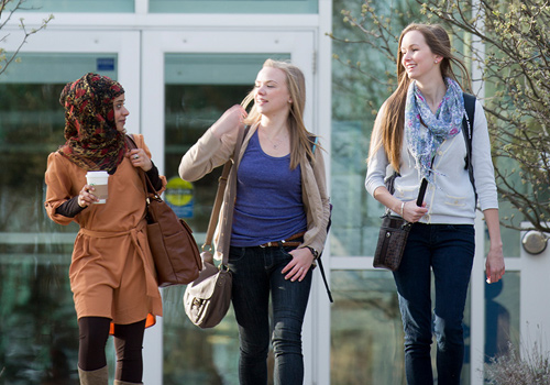 Three students walking on Brescia campus