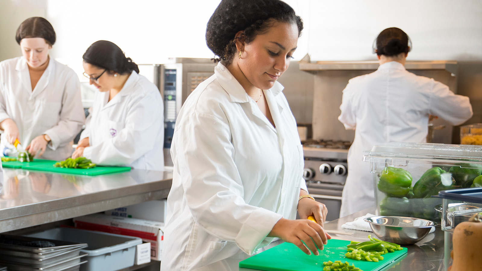 Students preparing food in commercial kitchen at Brescia