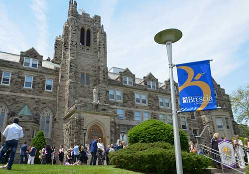 Brescia flag in front of Ursuline Hall during graduation.