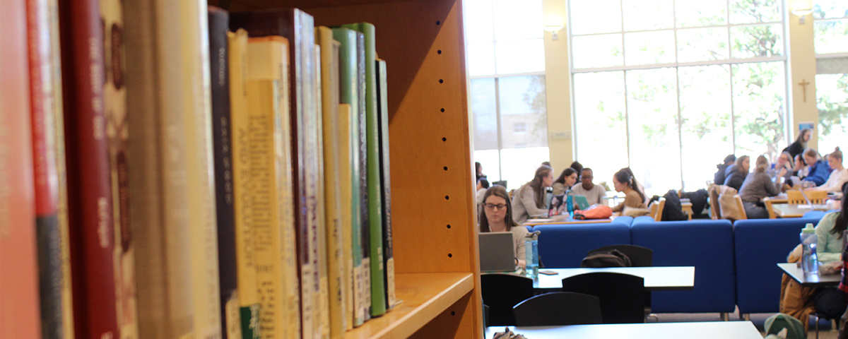 Library books in foreground with students sitting at tables in background.