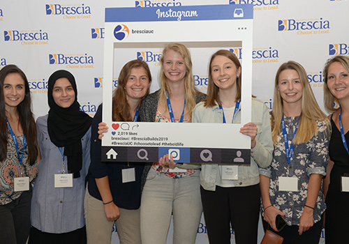 Students standing in front of Brescia selfie wall with Instagram profile cardboard cutout in front of them.