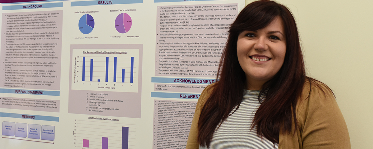 Student in front of research poster