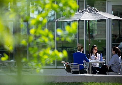 Three students sitting around a table talking and laughing under a patio umbrella on Brescia's campus.