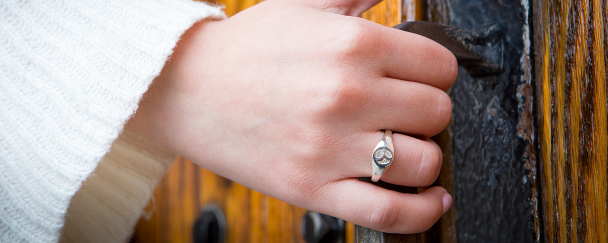 Student wearing alumane ring and opening door