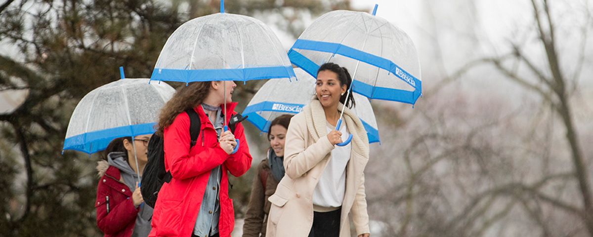 Students walking outside campus holding umbrellas