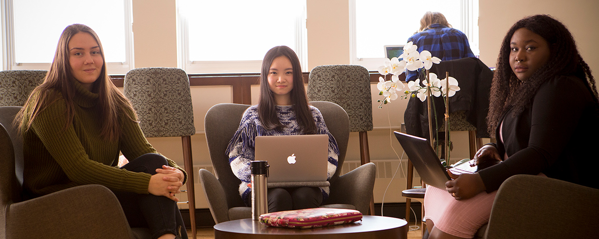 Students sitting and working on laptop in the Rose Room