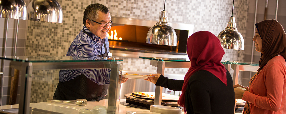 Tim D'Souza serving food to students in the Mercato