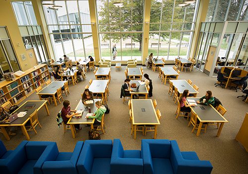 Students sitting in tables at Library