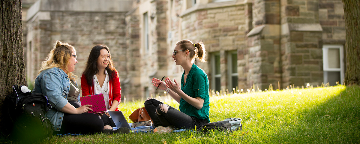 Three students sitting in the grass talking outside of Ursuline Hall.