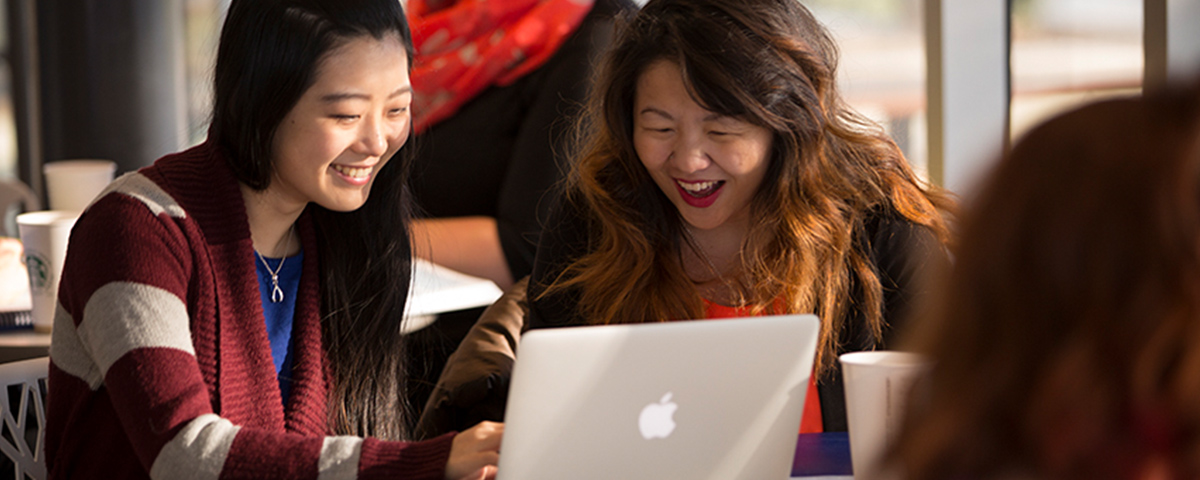 Two smiling students looking at a laptop together.
