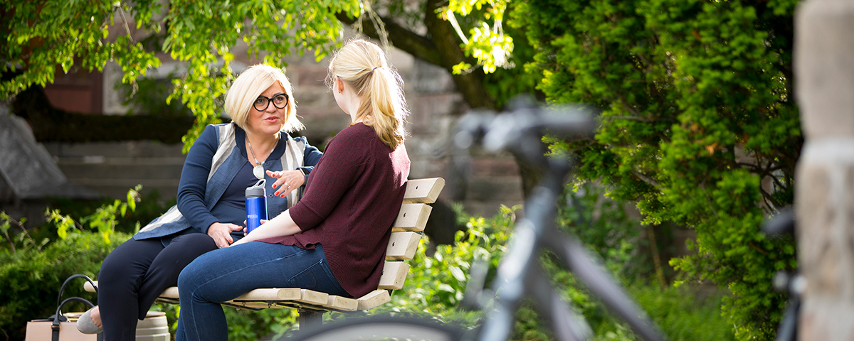 A student talking with a staff member on a bench.