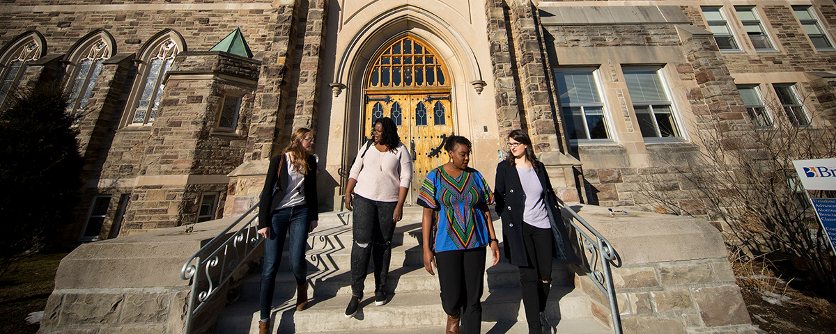 Four students walking down the steps of Ursuline Hall.