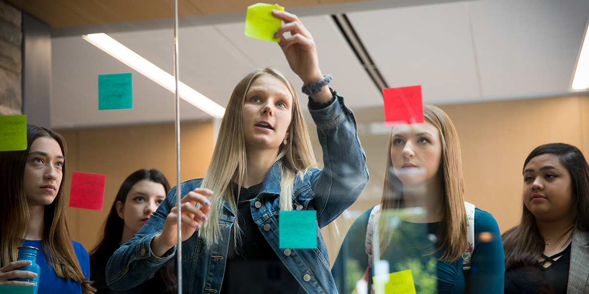 Students placing sticky notes on glass wall